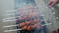 Male hands turn skewers with fried meat on brazier. Stock Footage