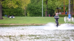 Male wakeboarder jumps during training on pond at park. Stock Footage