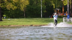 Male wakeboarder jumps and spins on a board at Putyaevsky pond Stock Footage