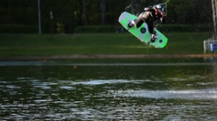 Male wakeboarder jumps on board during training at pond in park. Stock Footage