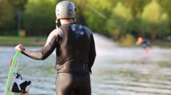 Male stands looking at the pond where another athlete performs. Stock Footage