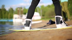 Legs of wakeboarder on board at pond shore before start performing Stock Footage