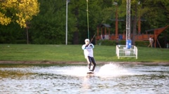 Male wakeboarder makes air raley during training at pond Stock Footage
