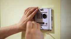 Worker mounts cover on external part of home intercom Stock Footage