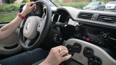 The woman drives a Fiat, speed switches and turn the steering wheel - stock footage