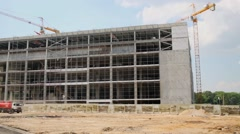 Panorama of construction site with building and two tower cranes Stock Footage