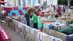Children and adults walk along maze constructed of books Stock Footage