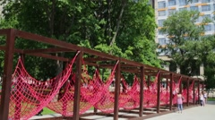 People on alley with hammocks and children playground Stock Footage