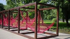 Hammocks woven from red ropes and suspended on frame in alley Stock Footage