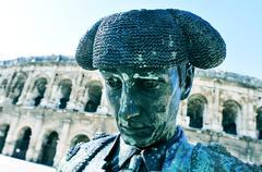 Statue of bullfighter Nimeno II and Roman amphitheatre in Nimes, France Stock Photos