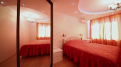 Stock Video Footage of Bedroom decorated in red tones, double bed, mirrored wardrobe