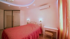 Stock Video Footage of Bedroom decorated in red tones with double bed covered by coverlet