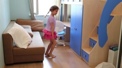 Little girl looks for where it is possible to hide in the room Stock Footage