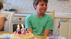 Boy sits at table with birthday cake decorated by burning candles Stock Footage