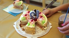 Sliced into pieces birthday biscuit cake on table in kitchen. Stock Footage