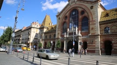 People and traffic pass by at the Market Hall in Budapest Stock Footage