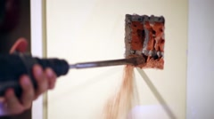 Worker makes hollow in brick under plaster on wall Stock Footage