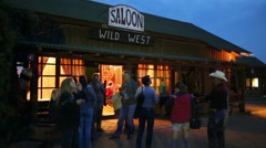 People stand near saloon Wild West at horse ranch Stock Footage