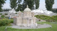 Turists walk through the miniatures of old Italian Chiesa in park Leolandia Stock Footage