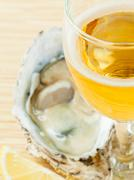 Fresh oysters with lemon and a glass of wine on a wooden table . - stock photo
