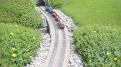 Small toy freight train travels by rail in the park Stock Footage