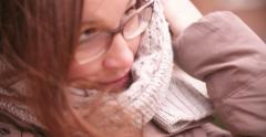 Woman wrapping around warm scarf during winter - stock footage
