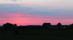 Silhouettes of buildings roofs and trees against red sunrise sky Stock Footage