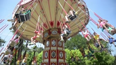 Bright carousel spinning with people against the backdrop of palm trees Stock Footage