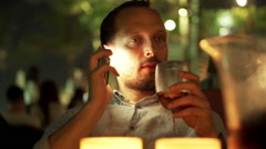 Young man talking on cellphone, drinking sangria at bar HD Stock Footage