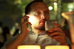 Young man talking on cellphone, drinking sangria at bar NTSC Stock Footage