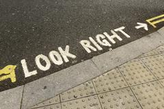 Look right lettering on road reference to left hand traffic London England Stock Photos