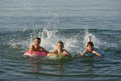Children on floating tyres in the sea Mediterranean near Fano Marche Adriatic Kuvituskuvat