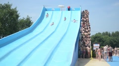 Children ride on the big slides in the water park - stock footage