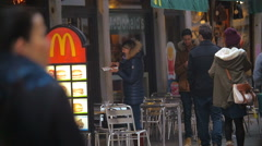 Woman Eating Fast Food by the Entrance to Restaurant Stock Footage