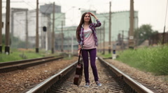 Girl walking on railway wish guitar Stock Footage