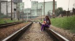Girl walking on railway wish guitar - stock footage