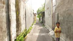 Walk through narrow alley, towards little indonesian boy, sunny day Stock Footage