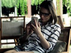 Woman texting, sending sms on smartphone in bar NTSC Stock Footage