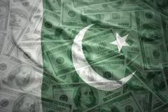 Colorful waving pakistani flag on a american dollar money background Stock Photos