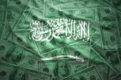 Colorful waving saudi arabia flag on a american dollar money background Stock Photos