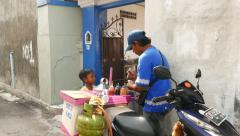 Bakso vendor on motorbike serve portion for little boy, small bystreet Stock Footage