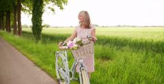 Mature woman standing with a vintage bicycle in a park Stock Footage