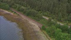 AERIAL United Kingdom-Steam Train Running Down Towards Loch Eil Stock Footage