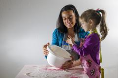 Girl 3 years and her mother baking mixing ingredients in a white bowl Stock Photos