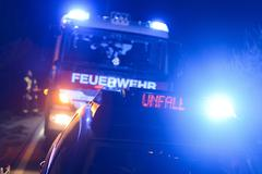 Fire engine and police car with flashing blue lights and the LED display Unfall - stock photo