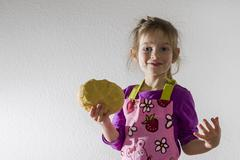 Girl 3 years baking holding a lump of dough in her hand Stock Photos
