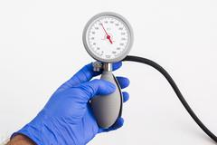 A hand with a blue medical glove is holding a sphygmomanometer blood pressure - stock photo