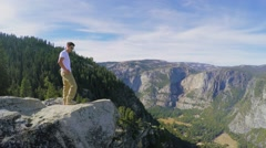 Tourist stands on rock near forest in Yosemite National Park - stock footage