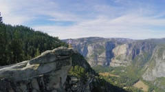 Tourist stands on top of rocky mountain in Yosemite National Park - stock footage