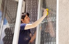 Woman washes a window pane Stock Photos